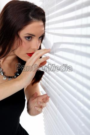 kobieta patrzac przez zaluzje