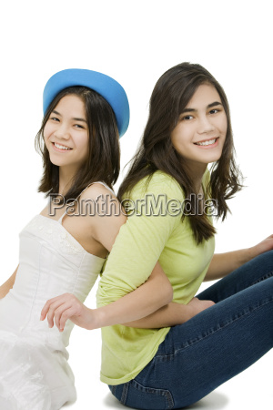 two sisters sitting together isolated on