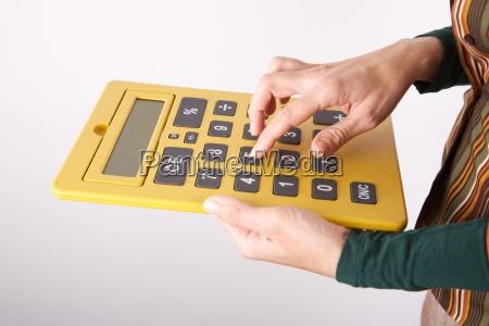 typing on big yellow calculator