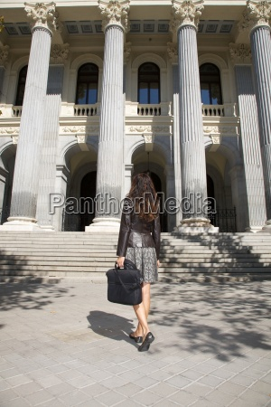 leather businesswoman in front of columns