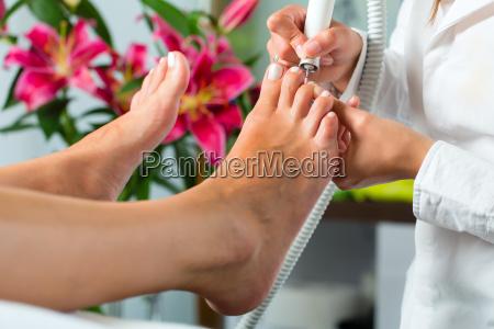 kobieta w salonie pieknosci dostaje pedicure