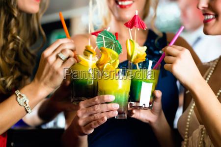 kobiety z koktajlami w klubie lub