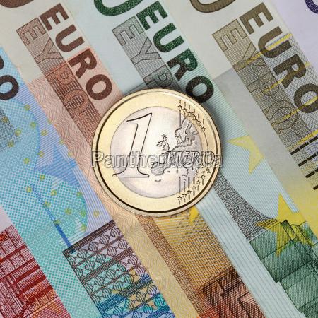 a euro coin on euro banknotes