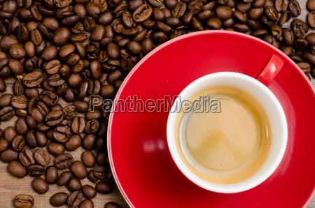 czerwona filizanka espresso i brazowych ziaren