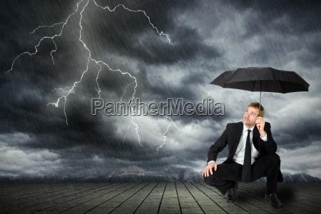 mezczyzna w garniturze i pod parasolem