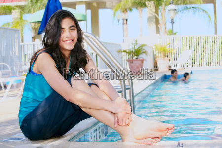 young teen girl sitting by pool