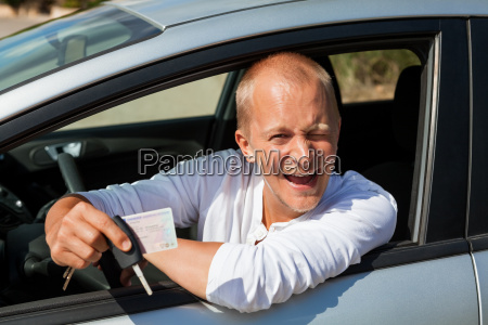 mlody dorosly czlowiek w nowym samochodzie