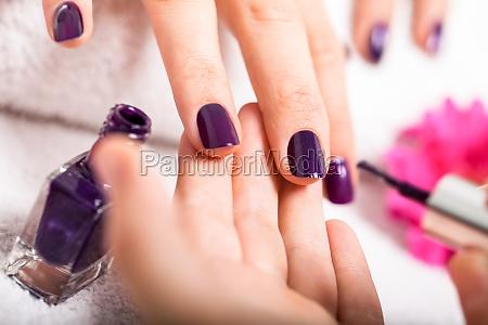 kobieta dostaje jej paznokcie na fioletowo
