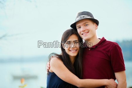young interracial couple hugging by lake
