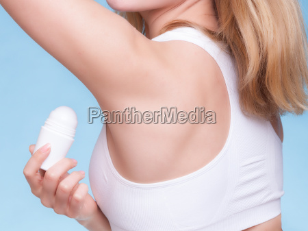 girl applying stick deodorant in armpit