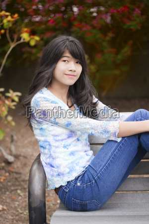 young preteen girl sitting on park