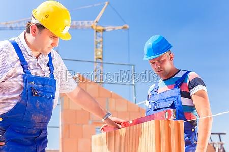 dwoch pracownikow budowlanych na budowie