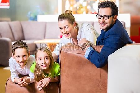 rodzina kupuje kanapie w sklepie meblowym
