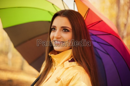 smiling woman standing under the umbrella