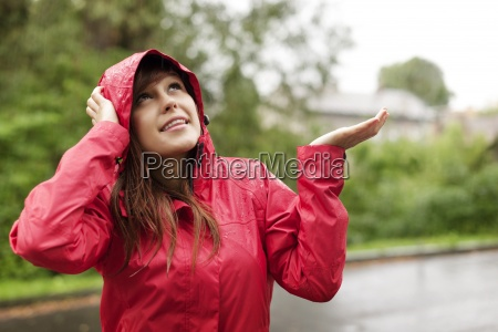 beautiful woman in raincoat checking for