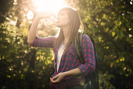 beautiful female hiker drinking water in