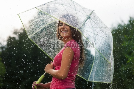 young woman standing in summer rain
