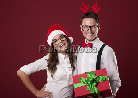 smiling nerd couple holding red christmas
