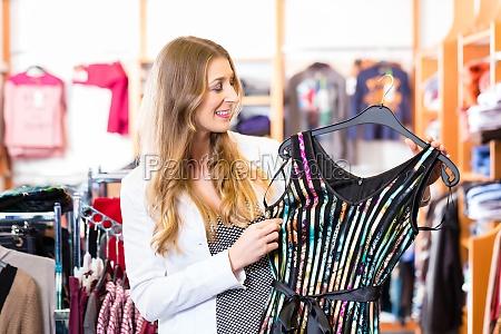 kobieta wybiera ubrania w sklepie podczas