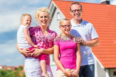 rodzina stoi dumnie przed domem