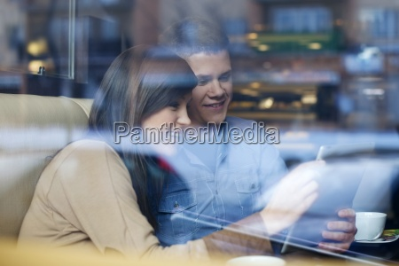 young couple using tablet in coffee