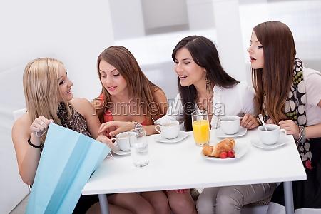 kobiety przyjaciol patrzac na zakupy