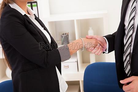 biznesowy mezczyzna i kobieta trzasc reki