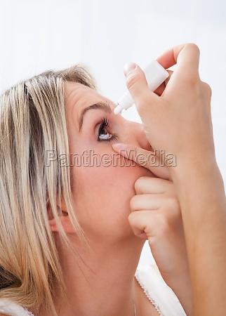 kobieta odlewania krople w oczy