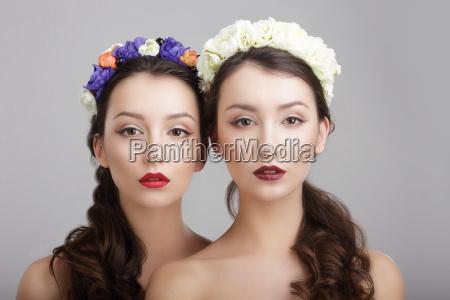 elegancji dwie kobiety z wiencami kwiatow