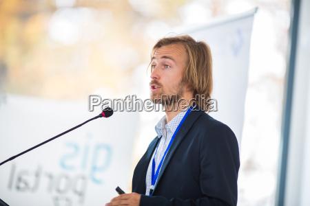 przystojny mlody czlowiek przemawia na konferencji