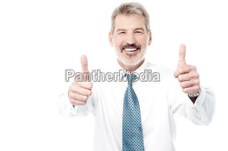 starszy mezczyzna pokazujac podwojne kciuki w