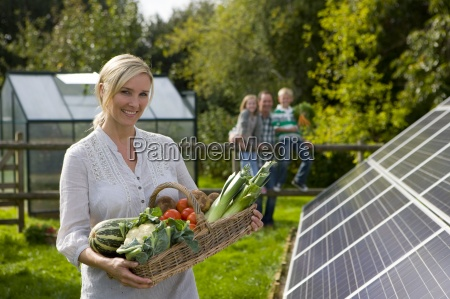 woman holding basket of vegetables near
