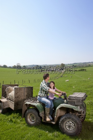 shepherd and daughter riding tractor pulling