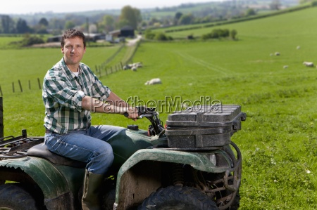 portrait of farmer riding tractor in