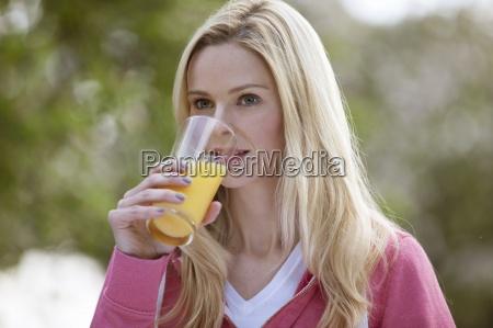 mloda kobieta pije szklanke soku pomaranczowego