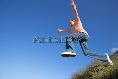 entuzjastyczna dziewczyna skoki przeciwko blekitne niebo