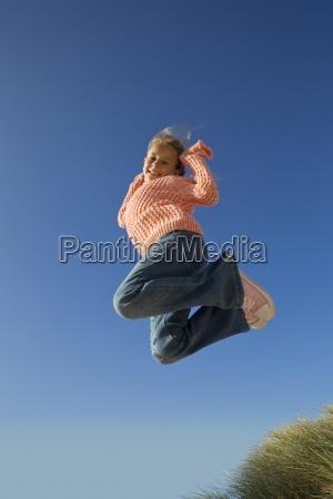 portret usmiechnieta dziewczyna skaczac z blekitnego