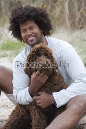 portret czlowieka siedzacego na plazy z