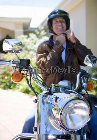 senior man siedzi na motorze na