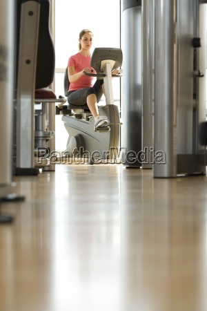 young woman on exercise machine in