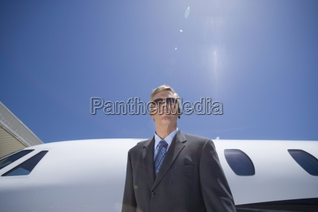 businessman in sunglasses by aeroplane low