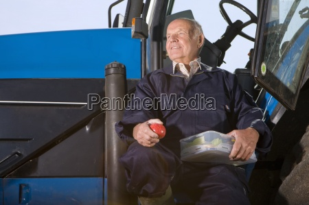 farmer holding apple and lunchbox on