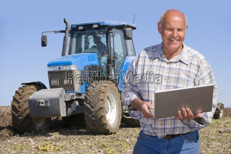 smiling farmer using laptop with tractor