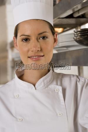 kobieta kucharz stojac w kuchni handlowych