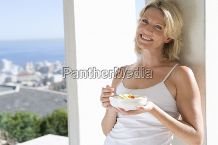 young woman eating fruit salad outdoors