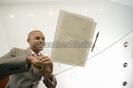 biznesmen piorem i dokumentacji na szklanym