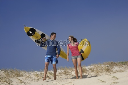 young couple carrying surfboards down sand