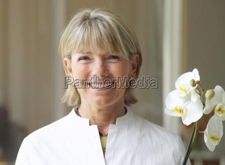 starszy kobieta trzyma kwiat usmiechniety widok