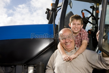 portrait of boy hugging grandfather by