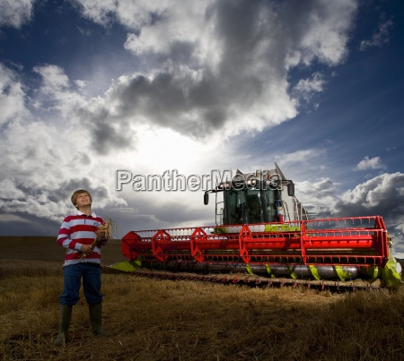 boy standing next to combine harvester
